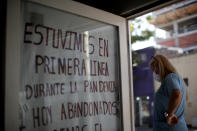 """Nurse Lidia Del Valle stands by a sign that says in Spanish """"We were on the front lines during the pandemic. Today, abandoned,"""" outside San Andres Clinic which has been occupied by its former workers since it closed at the start of the year following the death of the hospital's director and owner in Caseros, Argentina, Friday, April 30, 2021. While the pandemic has swelled the need for hospital beds, many private clinics say they're struggling to survive, citing the pandemic having pushed away many non-COVID patients and losing money on coronavirus sufferers because the government insurance program doesn't pay enough to meet costs. (AP Photo/Natacha Pisarenko)"""