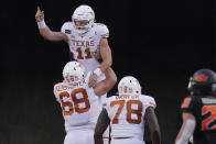 Texas quarterback Sam Ehlinger (11) celebrates a touchdown with offensive lineman Derek Kerstetter (68) and offensive lineman Denzel Okafor (78) in front of Oklahoma State linebacker Malcolm Rodriguez (20) during the second half of an NCAA college football game in Stillwater, Okla., Saturday, Oct. 31, 2020. (AP Photo/Sue Ogrocki)