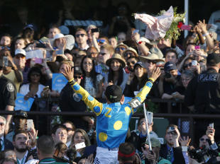 Victor Espinoza reacts to the crowd after guiding American Pharoah to win the Triple Crown. (AP)