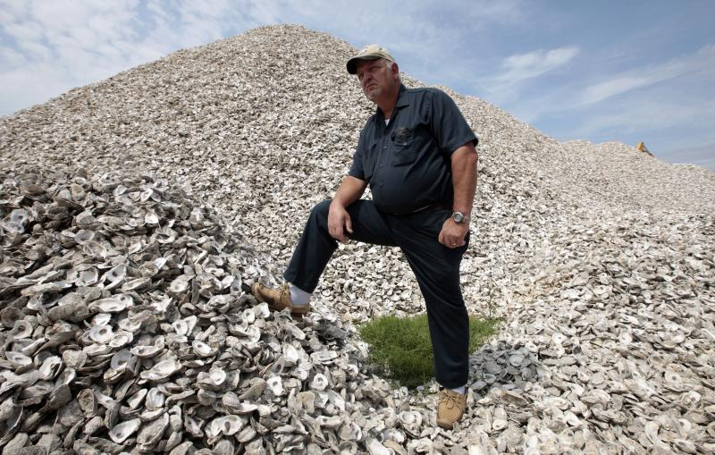 In this Thursday, April 14, 2011 picture, Mayor Stan Wright stands atop a pile of oysters in Bayou La Batre, Ala. The small fishing town is struggling to survive following the Deepwater Horizon oil spill that occurred nearly a year ago. (AP Photo/Dave Martin)