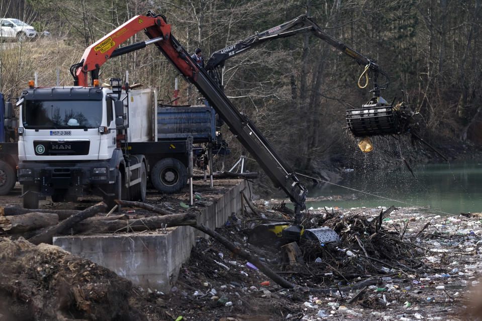 Cranes collect garbage from the Drina river near Visegrad, eastern Bosnia, Wednesday, Feb. 24, 2021. Environmental activists in Bosnia are warning that tons of garbage floating down the Balkan country's rivers are endangering the local ecosystem and people's health. The Drina River has been covered for weeks with trash that has piled up faster than the authorities can clear it out. (AP Photo/Kemal Softic)