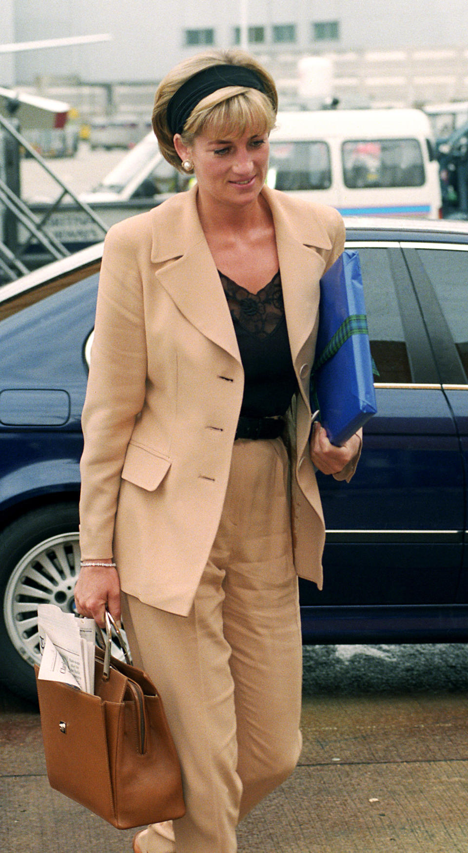 <p>This is by far one of our favourite looks. Here, Princess Diana is photographed at Heathrow Airport, as she prepares to board a flight to New York for a private preview of her dresses before they go to auction at Christie's. Diana opted for a camel two-piece suit finished with a sleek headband for the momentous occasion.<br><em>[Photo: PA]</em> </p>