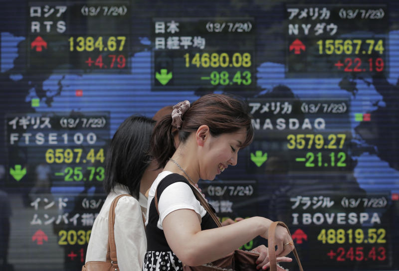 Women walk by an electronic stock board of a securities firm in Tokyo, Wednesday, July 24, 2013. Asian stock markets were mostly lower Wednesday after a survey showed Chinese manufacturing activity fell to its lowest point in nearly a year. Japan's Nikkei 225 fell 0.6 percent to 14,692.83. (AP Photo/Itsuo Inouye)
