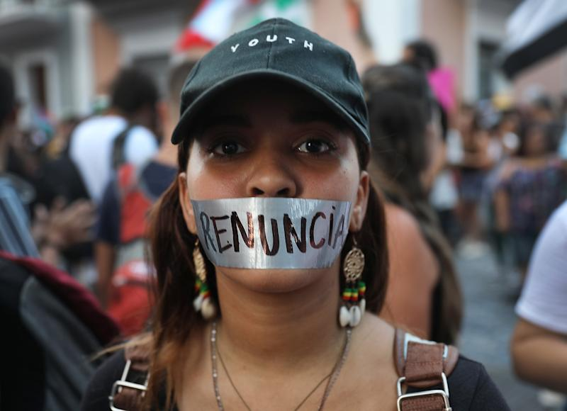 "Maria Linoshka, wearing tape over her mouth reading ""resignation"" in Spanish, joins with other protesters demonstrating along a street leading to the Governors mansion as they call for Puerto Rican Governor Ricardo Rossello to step down on July 16, 2019 in Old San Juan, Puerto Rico. (Photo: Joe Raedle/Getty Images)"
