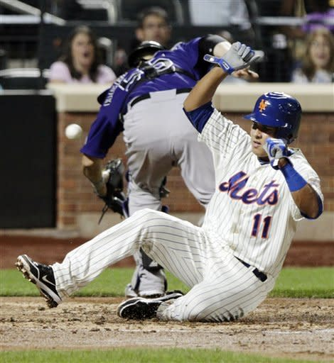 New York Mets' Ruben Tejada (11) slides past Colorado Rockies catcher Ramon Hernandez (55) to score on a sacrifice fly by Daniel Murphy during the fourth inning of a baseball game, Tuesday, Aug. 21, 2012, in New York. (AP Photo/Frank Franklin II)