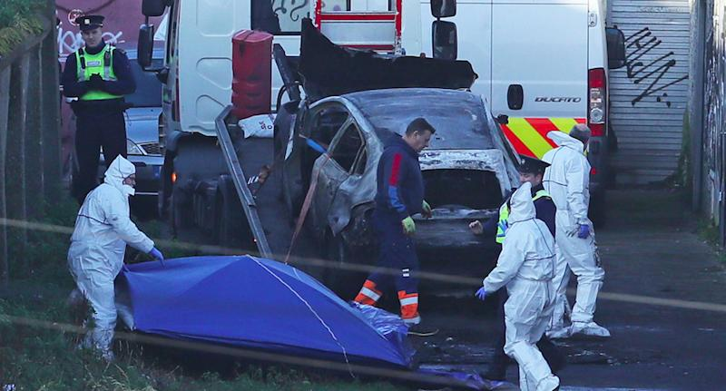 A burnt-out car on the back of a tow truck. The severed body parts of Keane Mulready-Woods were found in the car.
