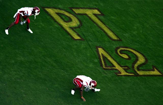 Members of the Washington State Cougars stretch in front of a memorial painted on the field for Pat Tillman #42 of the Arizona Cardinals during their Pac-10 game against the Arizona Sun Devils at Sun Devil Stadium/Frank Kush Field on November 13, 2004 in Tempe, Arizona. (Photo by Donald Miralle/Getty Images)