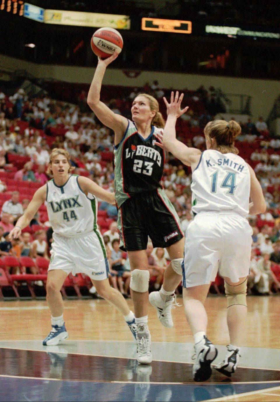 """FILE - In this July 17, 1999, file photo, New York Liberty forward Sue Wicks (23) shoots as Minnesota Lynx guard Katie Smith (14) and forward Angie Potthoff (44) move in to defend during the first half of a WNBA basketball game in Minneapolis. Wicks and Kym Hampton are """"Liberty Legends,"""" who have worked in the New York basketball community for years. (AP Photo/Adam M. Bettcher, File)"""