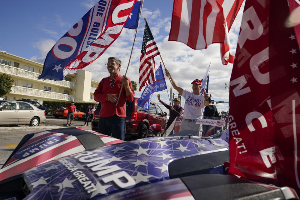 Supporters of President Donald Trump wave as they wait for the motorcade on the road to Mar-a-Lago, Trump's Palm Beach estate, on Wednesday, Jan. 20, 2021, in West Palm Beach, Fla. (AP Photo/Lynne Sladky)