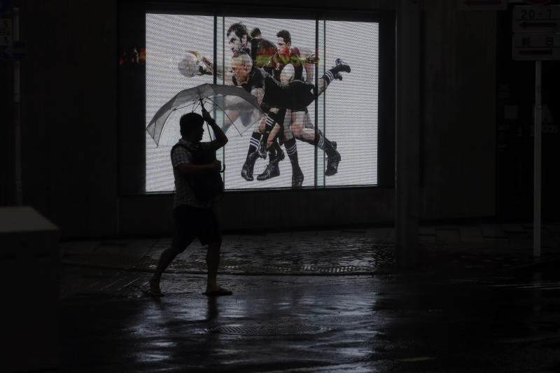 A man walks in rain in Shibuya district, Tokyo Saturday, Oct. 12, 2019. Tokyo as surrounding areas braced for a powerful typhoon forecast as the worst in six decades, with streets and trains stations unusually quiet Saturday as rain poured over the city. (AP Photo/Kiichiro Sato)