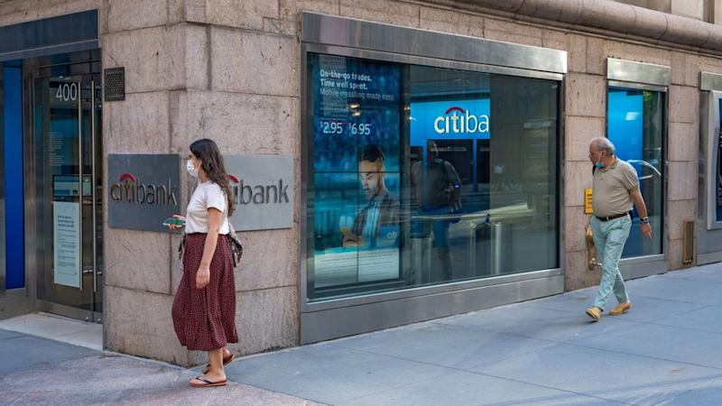 People in masks walk past a Citi ATM