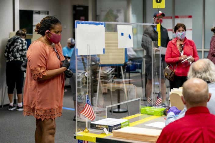 A woman waits to receive her ballot.