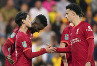 Liverpool's Takumi Minamino, left, celebrates scoring his side's third goal of the game with team-mates during the English League Cup third round soccer match at Carrow Road, Norwich, England, Tuesday Sept. 21, 2021. (Joe Giddens/PA via AP)