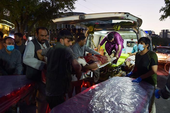 Volunteers and medical staff bring an injured man for treatment after two powerful explosions, which killed at least six people, outside the airport in Kabul on August 26, 2021. (Wakil Kohsar/AFP via Getty Images)