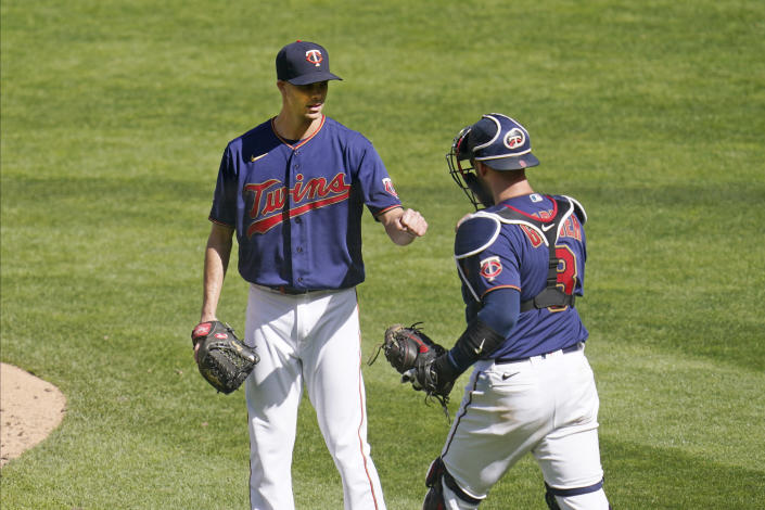 Minnesota Twins relief pitcher Taylor Rogers, left, and catcher Mitch Garver fist bump to celebrate the Twins 6-5 win over the Kansas City Royals in a baseball game, Saturday, May 29, 2021, in Minneapolis. Rogers earned the save. (AP Photo/Jim Mone)
