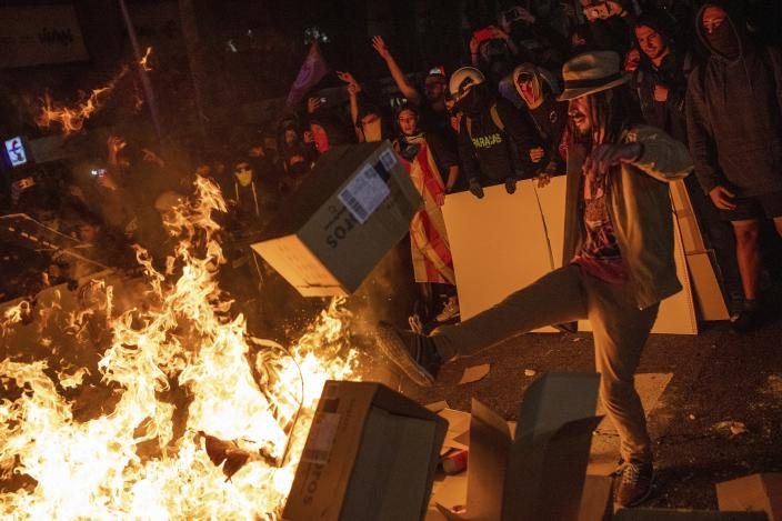 Protesters throw cartons to a burning barricade during clashes with police in Barcelona, Spain, Tuesday, Oct. 15, 2019. (Photo: Bernat Armangue/AP)