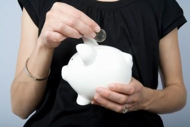 Woman putting money into piggy bank