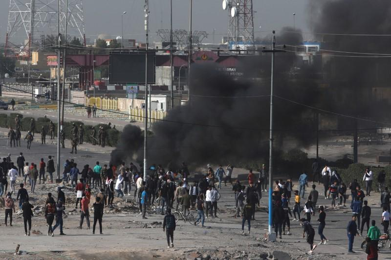 Smoke rises from burning tires as the demonstrators clash with Iraqi security forces during ongoing anti-government protests in Basra