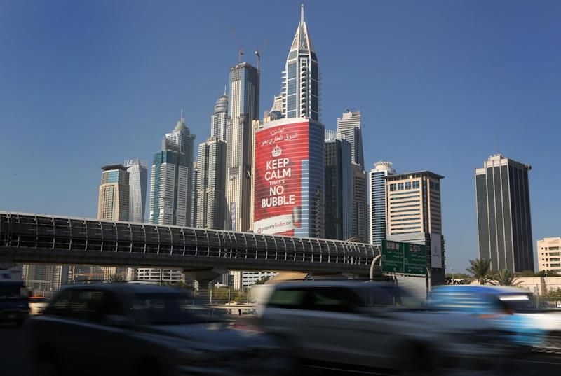 "In this Wednesday Nov. 13, 2013 photo, vehicles pass by a tower with a sign that reads, ""Keep Calm, No Bubble,"" at the Marina district in Dubai, United Arab Emirates. The logo for Dubai's bid to host the Expo 2020 reflects a push by the city's leaders to avert another financial crisis like the one that brought the city to its knees in 2008. Dubai saw property values slashed by more than half and the city's government needed a $10 billion bailout from oil-rich neighbor Abu Dhabi in 2009. (AP Photo/Kamran Jebreili)"