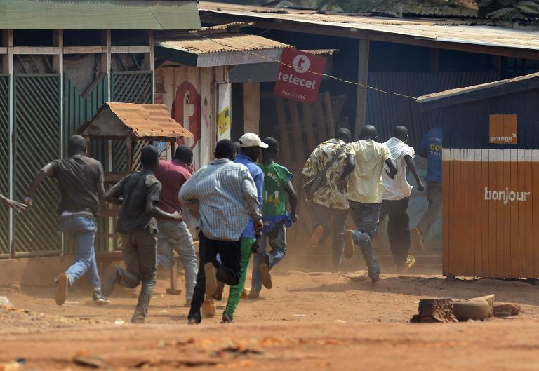 "Men run during a protest against the French ""Sangaris"" intervention in the Galabadia neighbourhood of Bangui on December 22, 2013"