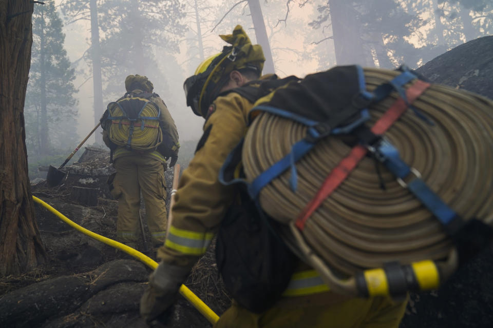 Two firefighters from Cosumnes Fire Department carry water hoses while holding a fire line to keep the Caldor Fire from spreading in South Lake Tahoe, Calif., Friday, Sept. 3, 2021. Fire crews took advantage of decreasing winds to battle a California wildfire near popular Lake Tahoe and were even able to allow some people back to their homes but dry weather and a weekend warming trend meant the battle was far from over. (AP Photo/Jae C. Hong)