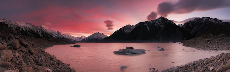 A pinky-reddish sunrise view at Tasman Glacier in Mount Cook National Park with lenticular clouds hovering all above the Mount Cook mountain range.