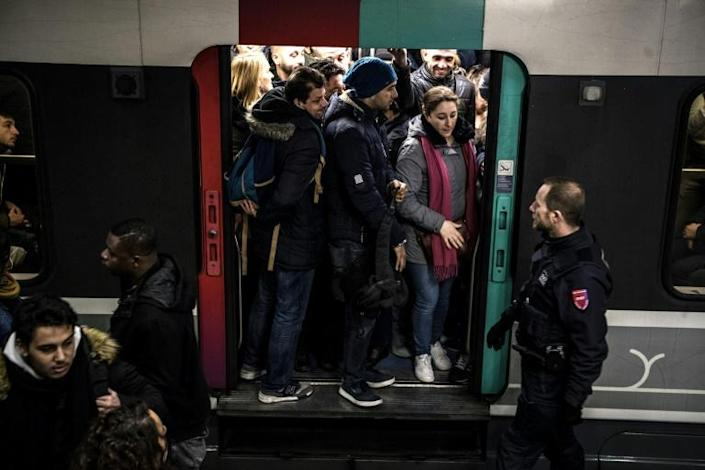 Security agents monitored packed suburban rail trains at the Gare du Nord station in Paris on Friday, during the ninth day of a public transport strike over pension overhauls. (AFP Photo/Christophe ARCHAMBAULT)