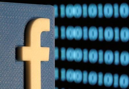 A 3-D printed Facebook logo is seen in front of displayed binary code in this illustration picture