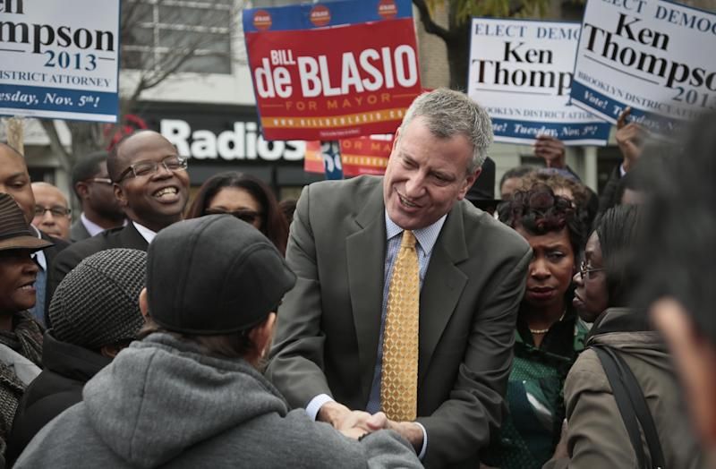 Democratic mayoral candidate Bill de Blasio, center, accompanied by Ken Thompson, fifth from right, candidate for Brooklyn district attorney, meet potential voters on Tuesday, Nov. 5, 2013, in the Crown Heights section of New York's borough of Brooklyn. De Blasio, 52, seems poised to become the first Democrat elected mayor in more than a generation, replacing Michael Bloomberg who helmed the nation's biggest city for 12 years. (AP Photo/Bebeto Matthews)