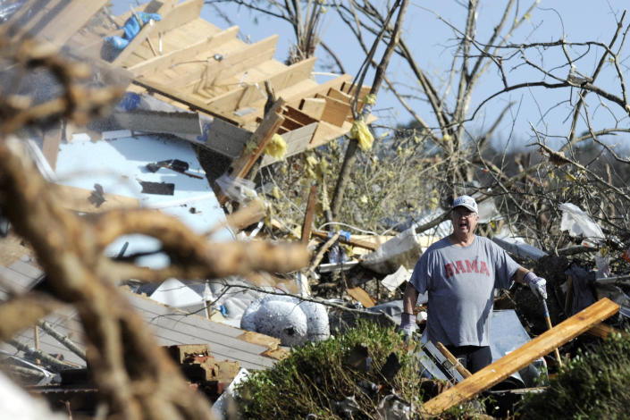 Retired firefighter Clyde Crump yells for help while working at the home of his daughter and son-in-law on Tuesday, Jan. 26, 2021, after it was destroyed by a tornado that hit Fultondale, Ala. The family survived by huddling in a basement storm shelter. (AP Photo/Jay Reeves)
