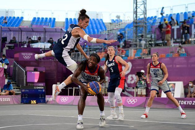 With almost no audience to cheer them on, France's Laetitia Guapo, left, fights for the ball with Team USA's Jacquelyn Young, center, during the women's semifinal 3x3 basketball match on July 28, 2021. (Photo: JAVIER SORIANO via Getty Images)