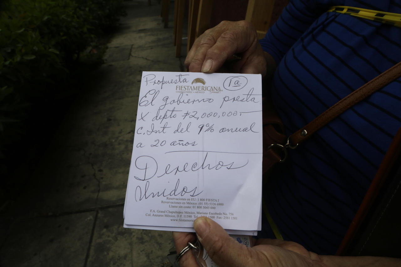 "In this Oct. 17 photo, Maria Luisa Campuzano Fernandez shows a handwritten note on hotel stationary describing the government's offer to lend money to residents like her whose homes were damaged by the earthquake one month ago at 275 Monterrey street in the Roma neighborhood of Mexico City. The note reads in Spanish: ""Proposal. The government lends per apartment 2,000,000 Mexican pesos (about 106,000 dollars) with 9 percent interest for 20 years. Rights included."" (AP Photo/Marco Ugarte)"