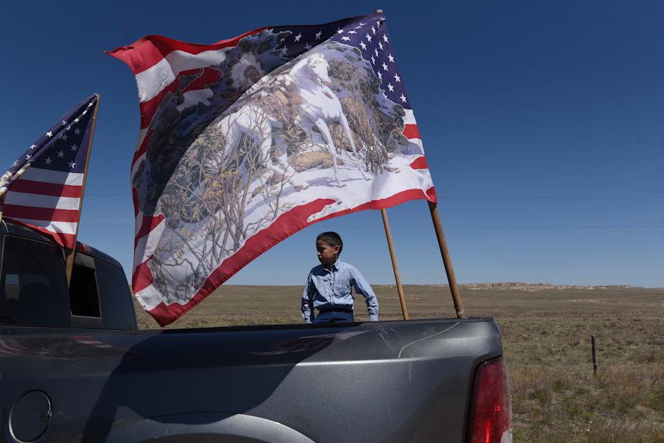 A young boy sits in the back of a pick up truck with the flags representing the United States and Native Americans near Fort Laramie, Wyoming. (Photo: REUTERS/Stephanie Keith)