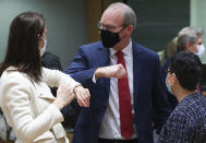 Belgium's Foreign Minister Sophie Wilmes, left, greets Ireland's Foreign Minister Simon Coveney, center, with an elbow bump during a meeting of EU foreign ministers at the European Council building in Brussels, Monday, Feb 22, 2021. European Union foreign ministers on Monday will look at options for imposing fresh sanctions against Russia over the jailing of opposition leader Alexei Navalny as the 27-nation bloc considers the future of its troubled ties with the country. (Yves Herman, Pool via AP)