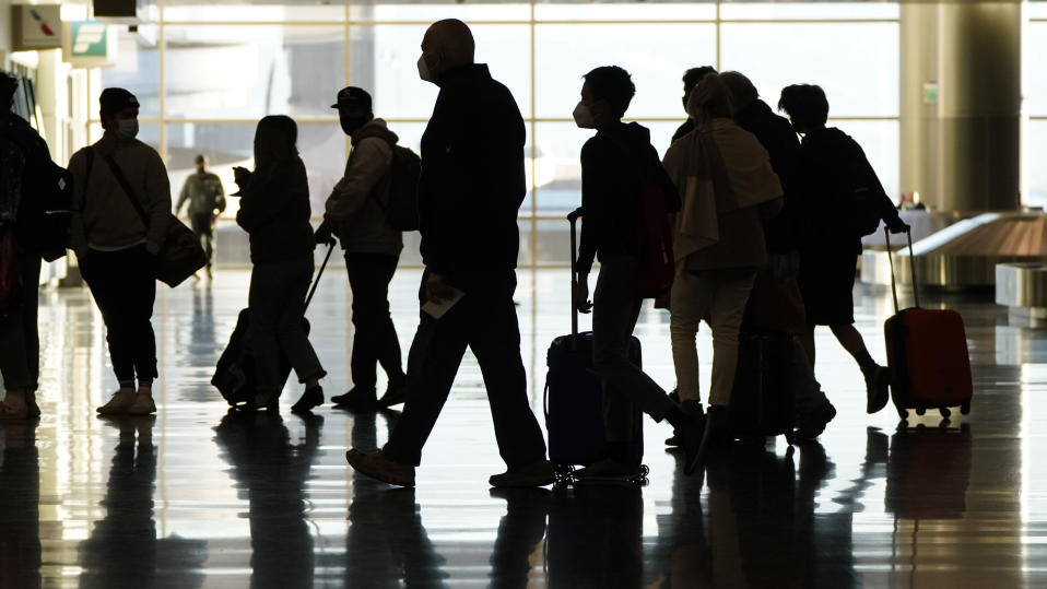 FILE - In this Nov. 25, 2020, file photo, air travelers line up to go through a a security checkpoint at Salt Lake City International Airport in Salt Lake City. Data from roadways and airports shows millions could not resist the urge to gather on Thanksgiving, even during a pandemic. (AP Photo/Rick Bowmer, File)