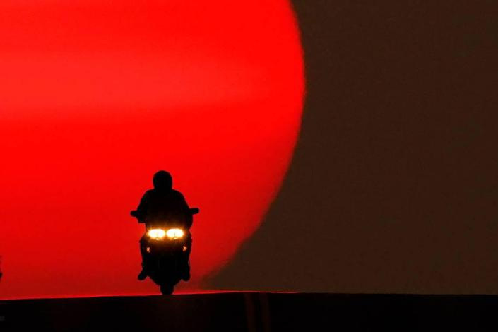 A motorcyclist is silhouetted against the setting sun Sunday in Shawnee. Sunsets have been more vibrant than normal recently as smoke from western wildfires drifts across the United States.
