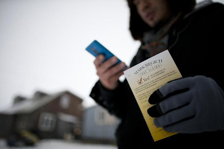 In this Oct. 9, 2014 photo, campaign worker Gabe Tegoseak makes a note on a list of voters he keeps on his phone as he gets a promise card to vote for Sen. Mark Begich from a resident while canvassing in Barrow, Alaska. Democrats hope to benefit from the addition of nearly 130 early voting sites this year, nearly all in rural communities that in the past had to mail-in ballots, or fly or drive to another community. (AP Photo/Gregory Bull)