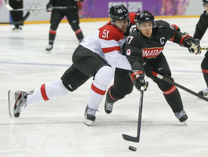 Canada forward Sidney Crosby gets tangled up with Latvia forward Koba Jass in the first period of a men's ice hockey game at the 2014 Winter Olympics, Friday, Feb. 14, 2014, in Sochi, Russia. (AP Photo/Mark Humphrey)