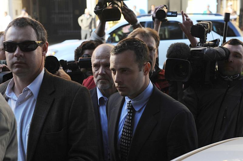Oscar Pistorius, center, arrives at the magistrates court in Pretoria, South Africa, followed by his uncle, Arnold Pistorius, back left, Tuesday June 4, 2013. Pistorius is accused of the shooting death of his girlfriend Reeva Steenkamp on Valentine's Day, Feb 14. (AP Photo)