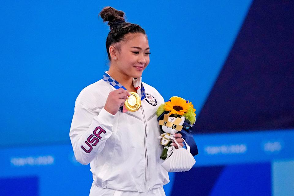 Suni Lee celebrates winning the gold medal in the individual all-around final.