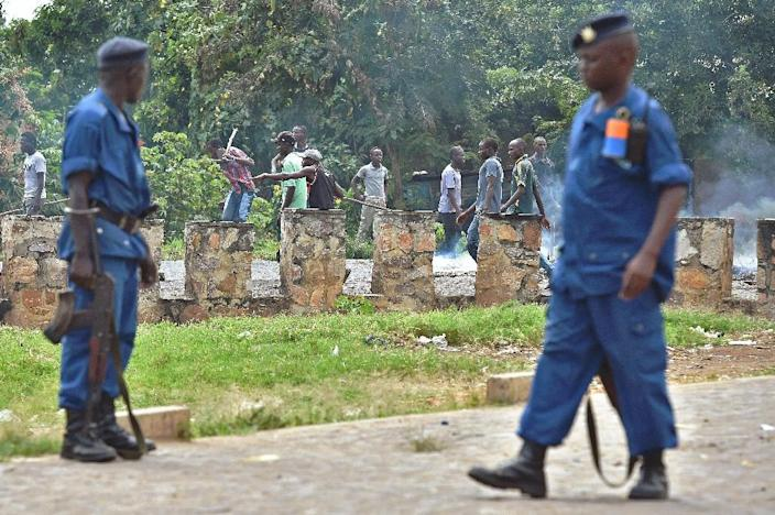 Policemen watch as members of the Imbonerakure, armed with sticks, destroy barricades erected by protestors opposed to the Burundian president's third term in the Kimana neighborhood of Bujumbura on May 25, 2015 (AFP Photo/Carl De Souza)