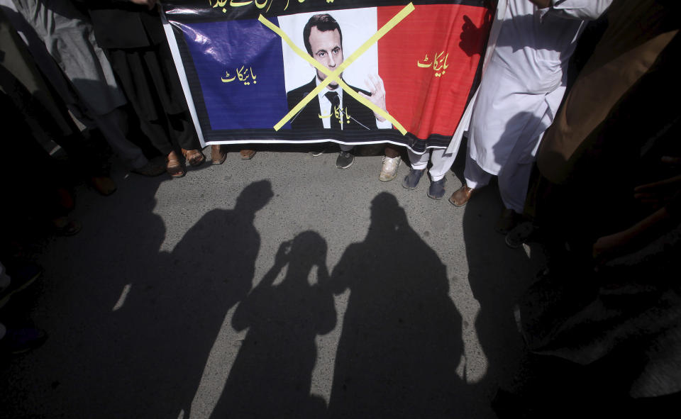 """Supporters of the religious student group, Islami Jamiat Tulba, hold a representation of the French flag with a defaced image of French President Emmanuel Macron and Urdu writing which reads, """"Down with France,"""" during a protest against the publishing of caricatures of the Prophet Muhammad they deem blasphemous, in Peshawar, Pakistan, Tuesday, Oct. 27, 2020. (AP Photo/Muhammad Sajjad)"""