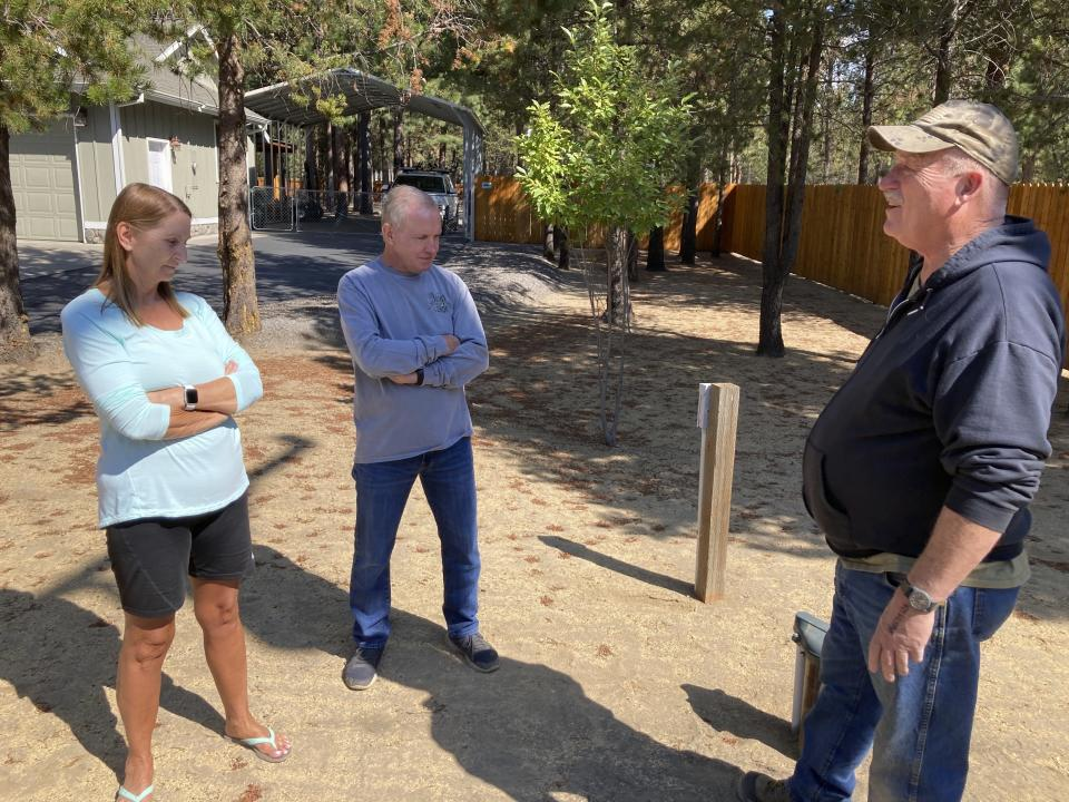 Left to right, Cindy and Jim Hooper and Rodger Jincks discuss water issues in their neighborhood in La Pine, Ore., on Aug. 26, 2021. Jincks' well ran dry and was having a new one drilled, and the Hoopers worry their well will also go dry as the water table lowers. Sheriff's deputies busted an illegal marijuana grow a block away recently and another, bigger grow had been nearby, using water from the same aquifer that the neighborhood uses. (AP Photo/Andrew Selsky)