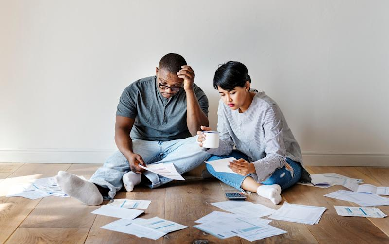 Two people sitting on the ground looking stressed while surrounded by papers.