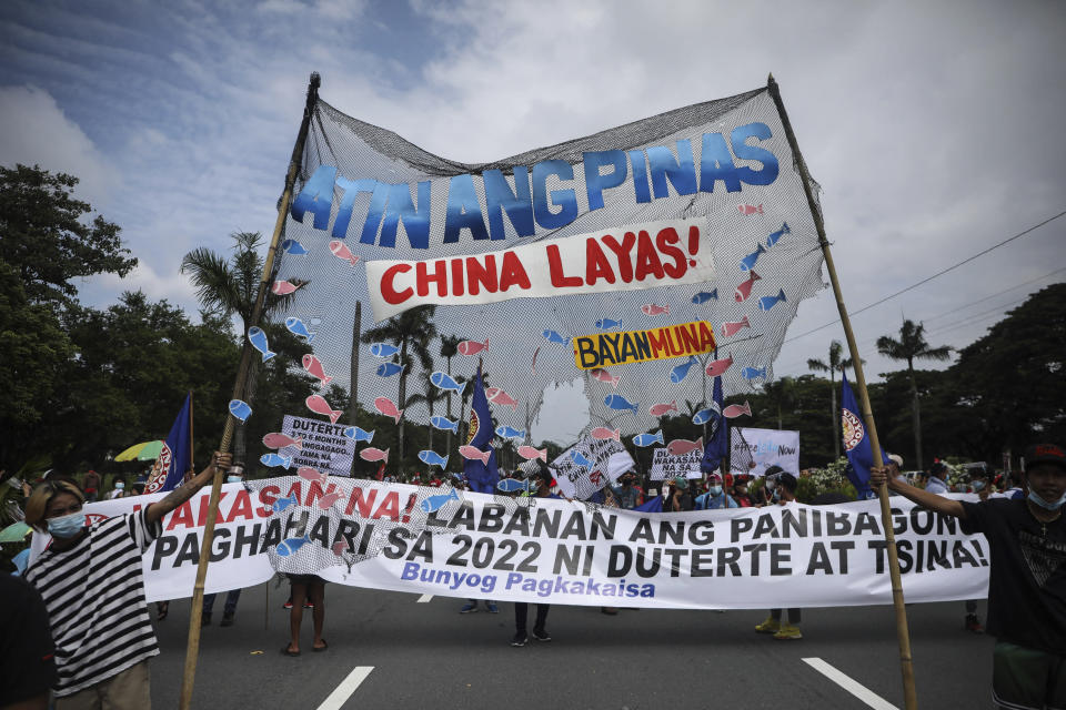 """Protesters hold a slogan that reads """"Philippines is ours, China get out!"""" as they tried to march towards the House of Representative where Philippine President Rodrigo Duterte is set to deliver his final State of the Nation Address in Quezon city, Philippines on Monday, July 26, 2021. Duterte is winding down his six-year term amid a raging pandemic and a battered economy. (AP Photo/Gerard Carreon)"""