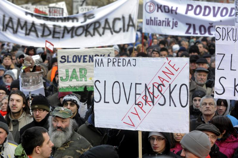 "FILE - This is a Friday, Feb. 10, 2012 file photo of demonstrators during a march against corruption in politics, in the center of Bratislava  with a banner that reads: ""For Sale – Slovakia – Sold out"".  For two years, the dossier claims, politicians of all stripes were pocketing kickbacks from members of an influential private investment group. In the wall of the apartment where the clandestine meetings took place was a listening device planted by a secret agent intrigued by why so many high-level visitors were dropping in. The ""Gorilla"" files _ mysteriously posted online by an anonymous source in December and said to be based on  the wiretaps _ have rocked the already-raucous world of Slovak politics ahead of elections Saturday. The fallout looks certain to propel populist former leader Robert Fico back into power, even though he himself has been implicated. (AP Photo/CTK, Jan Koller, File) SLOVAKIA OUT"