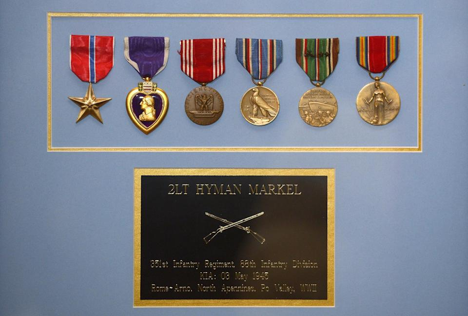 A plaque that contains medals, from left, the Bronze Star, the Purple Heart, the Army Good Conduct Medal, American Campaign Medal, European-African-Middle Eastern Campaign Medal and the World War II Victory Medal are seen after they were presented to Hyla Merin along with a Silver Star by Army Capt. Zachariah L. Fike, Sunday, Feb. 17, 2013, during a ceremony at her home in Thousand Oaks, Calif. The medals were presented posthumously to her father after recently being discovered in an apartment where Merin's mother and aunts had once lived. (AP Photo/Mark J. Terrill)