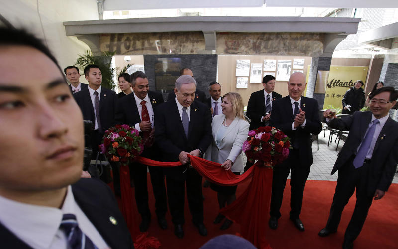 FILE - In this May 7, 2013 file photo, Israeli Prime Minister Benjamin Netanyahu, center left, and his wife Sara, center right, attend the ribbon cutting ceremony at the Shanghai Jewish Refugees Museum in Shanghai, China. As his government is slashing welfare benefits and hiking takes for the working class to overcome a huge deficit, Israeli Prime Minister Benjamin Netanyahu is finding himself under fire again for his lavish lifestyle. (AP Photo/Eugene Hoshiko, File)