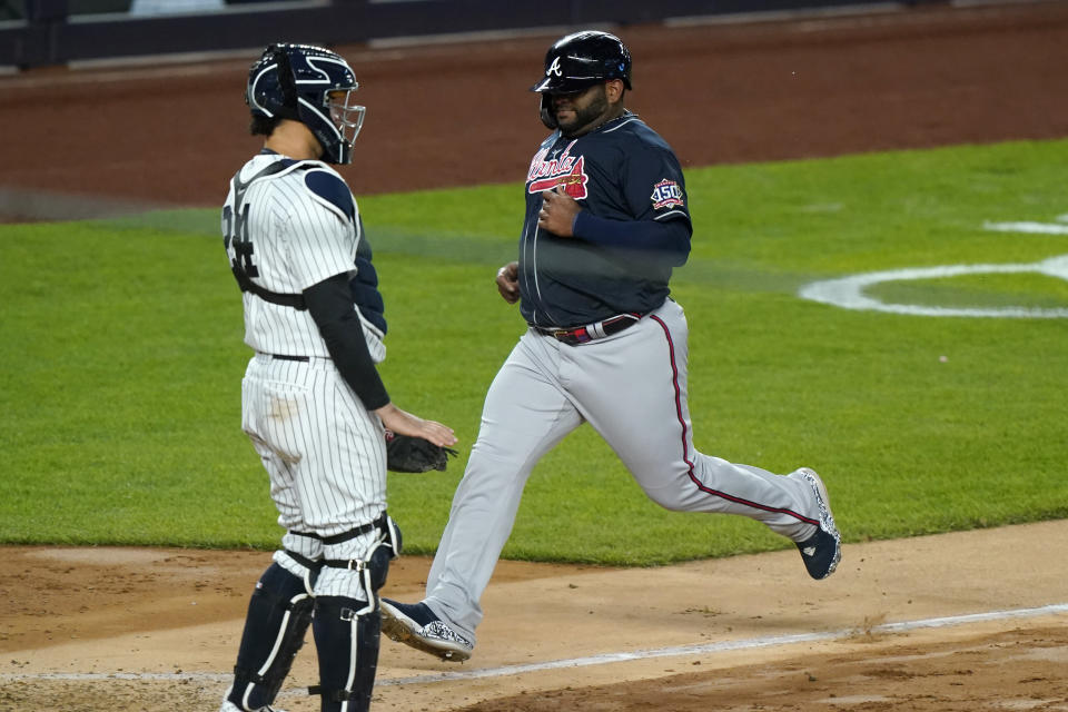 Atlanta Braves' Pablo Sandoval scores on Ehire Adrianza's fifth-inning sacrifice fly, next to New York Yankees catcher Gary Sanchez in a baseball game Wednesday, April 21, 2021, at Yankee Stadium in New York. (AP Photo/Kathy Willens)