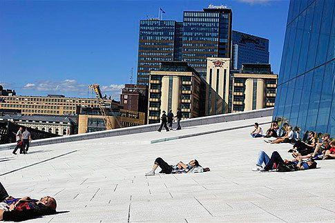 People sunbathe in front of the Oslo Opera House. Photo: Reuters